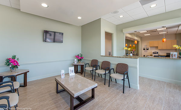 Waiting Area with Reception Desk in the Background at Sage Dental Oviedo