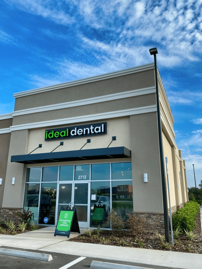 The front exterior of Ideal Dental in Osceola County showing the black awning and Ideal Dental signage.